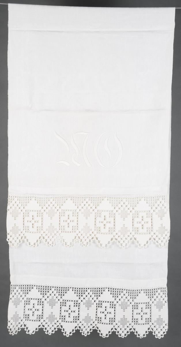 Hvit pyntehåndduk hvor kortsidene er brettet inn og sydd til med maskin. Heklet bord er sydd på for hånd i hver kortside. Broderte initialer i tykksøm.