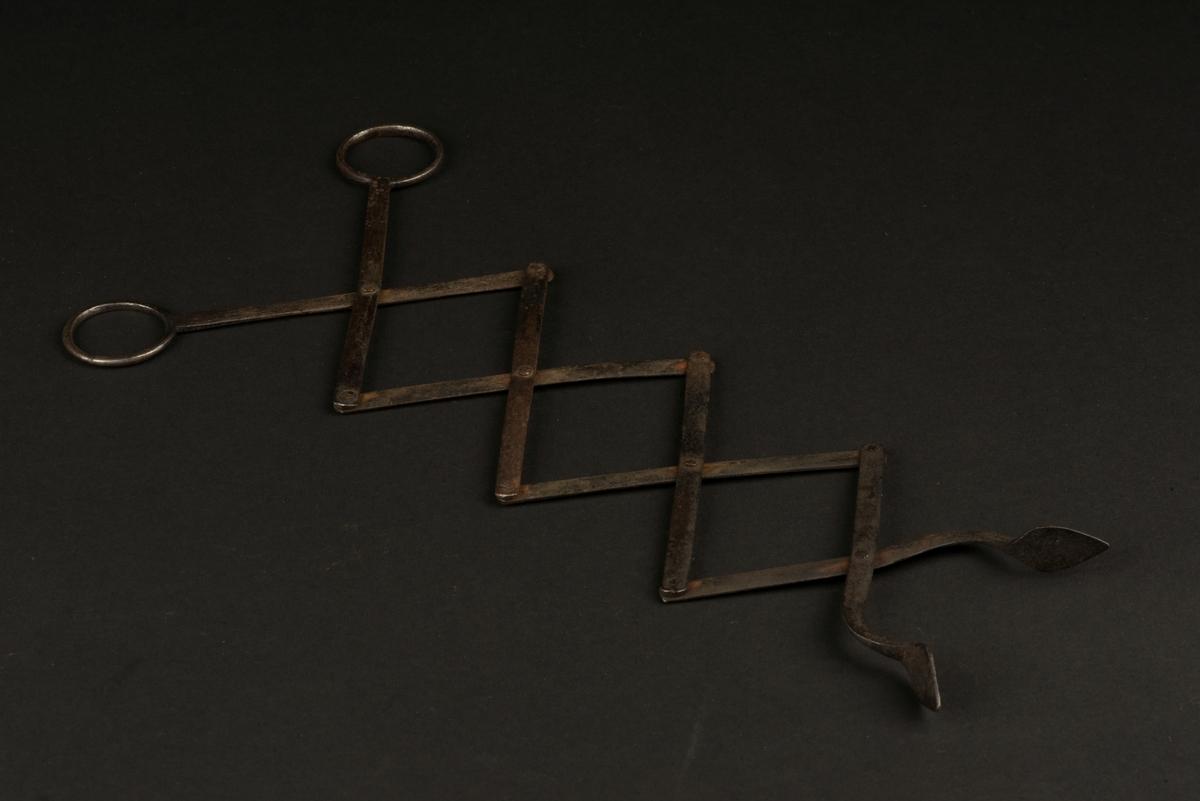 Eldtäng av järn. Tången är utformad som en sax som går att sträcka ut och fälla ihop då den är ledad. Handtag med öglor.