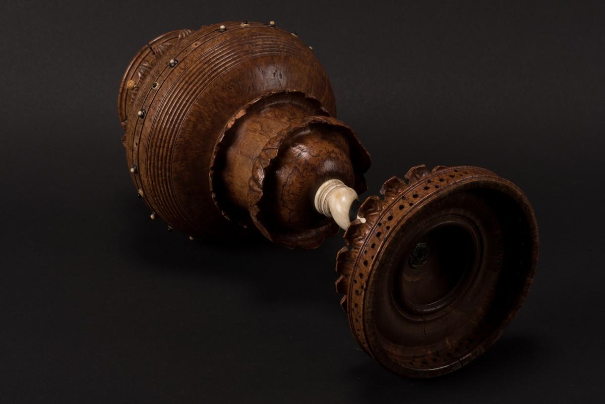Kärl i form av en pokal av svarvad masurbjörk. Pokalen är prydd med skuren dekor samt dekorerad med benknoppar i svart och vitt. Benet är spiralvridet och tillverkat av ben, ofärgat samt infärgat med svart. Upptill finns en löstagbar krans och inuti en sil med perforerad botten.