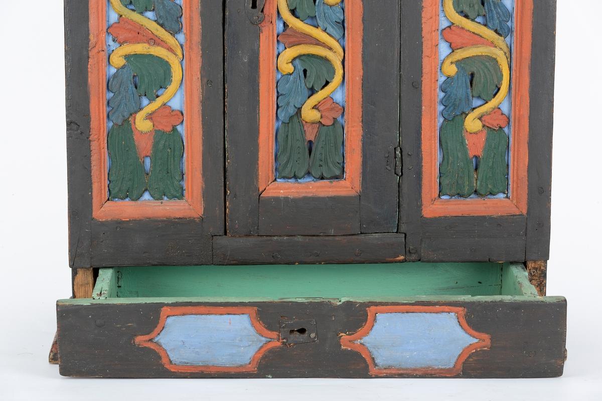 Skap. Hengeskap. Furu. Utskkåret og malt dekor. Gesims, håndskåret, gjennombrutt ranke. malt. Dør og dekorfelt på hver side skåret og malt. Skuff underskapet med symmetrisk skåret og malt felt. Skapet har innvendig 1 hylle. Skuff og skap er innvendig grønnmalt.  Skapet er gammelt, antakelig 1800 tallet.