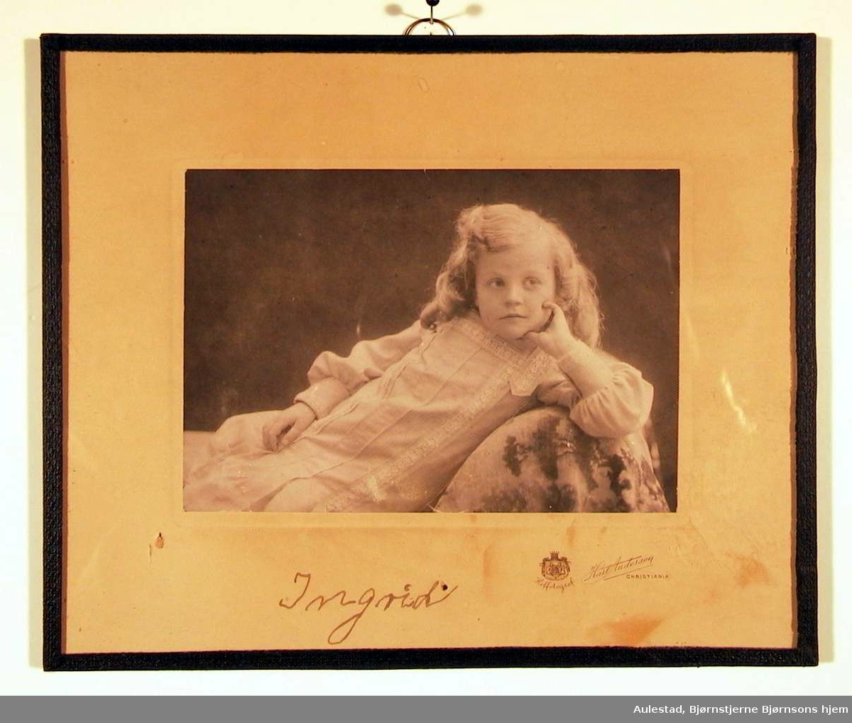 Barneportrett av stor pike liggende henslengt på divan- sofa med den ene hånden under kinnet.