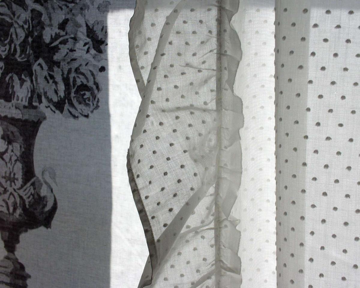 Et gardinfag med kappe sydd i hvitt gjennomsiktig bomullsstoff med prikker.