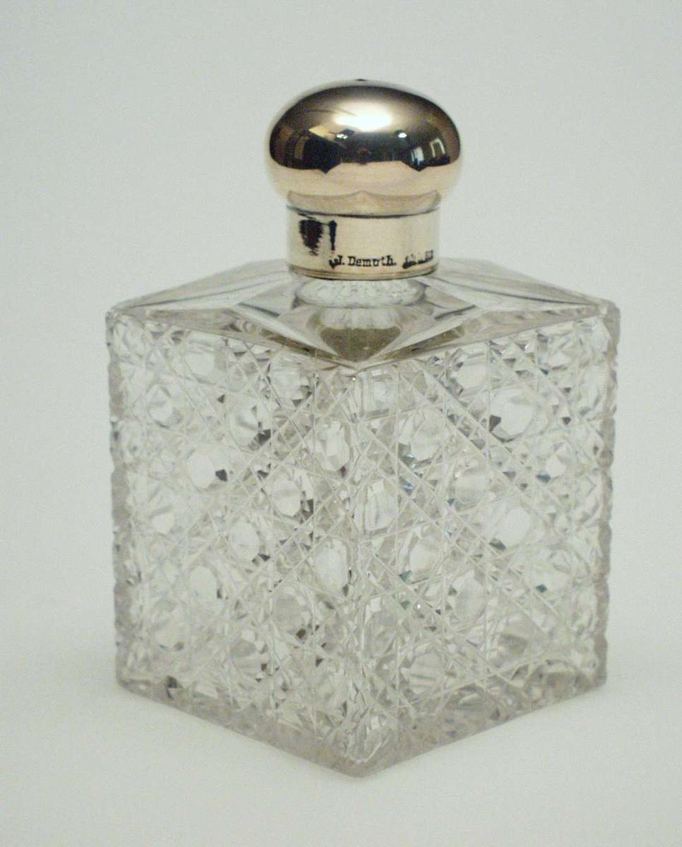 Firkantet flaske i krystall med skjærslipt dekor. Flasken har en rund kork i sølv.