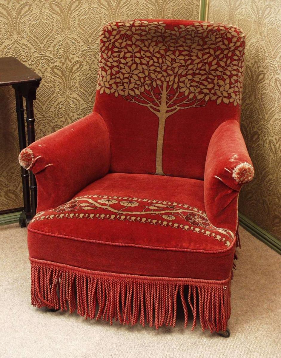 Lenestol med trinne profilerte ben, utstyrt med hjul. Stolen er trukket med rød plysj. Den har tremotiv i ryggen og bladverk langs setet i gult. Røde tvinnede frynser skjuler benene.