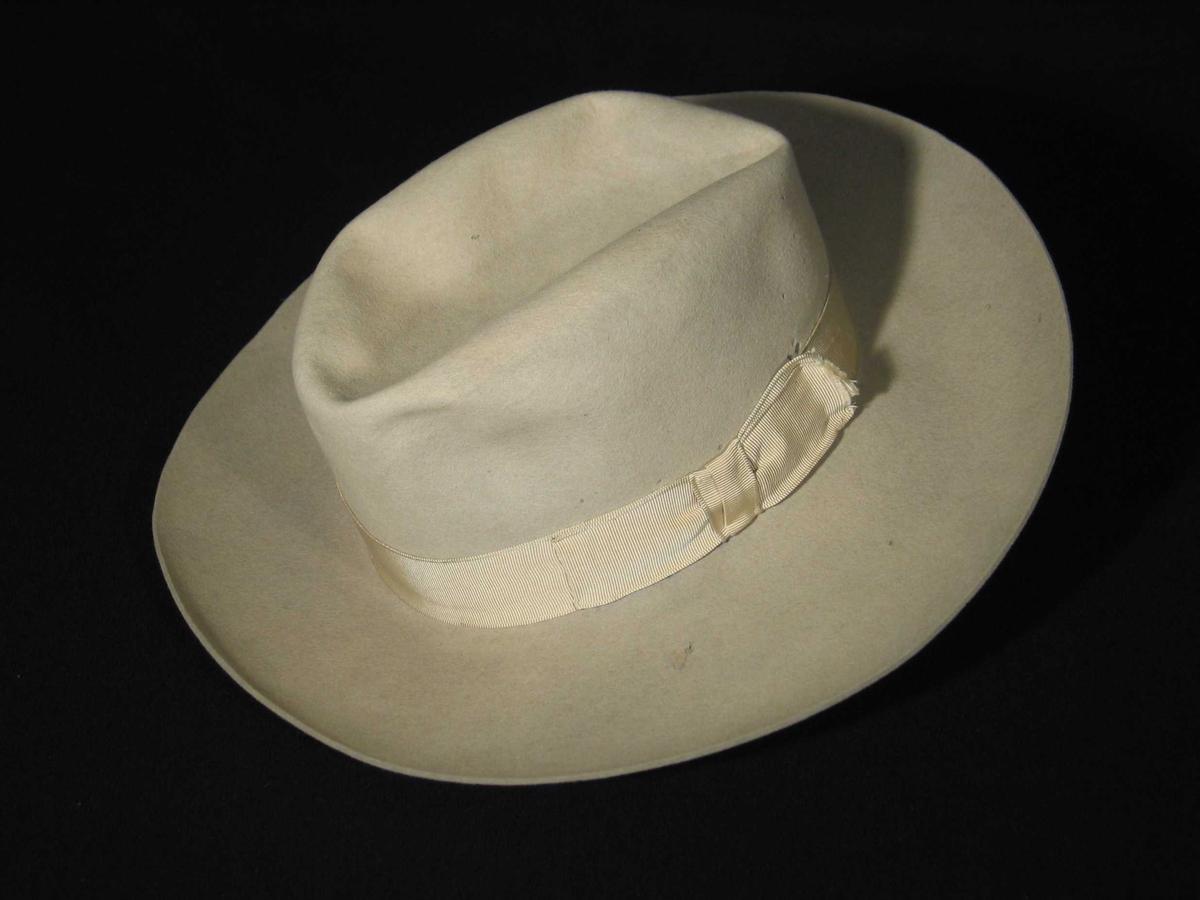 Lys grå hatt av ullfilt med 4cm bredt ripsbånd nederst mot brem, sløyfe på venstre side. På innsiden nederst langs kanten er satt en 5 cm bred svetterem av brunt skinn. Pull og brem er formet av en kappelin. Pullen er myk og kan formes. Firmamerke, trykt på tøy og limt i hattebunnen.