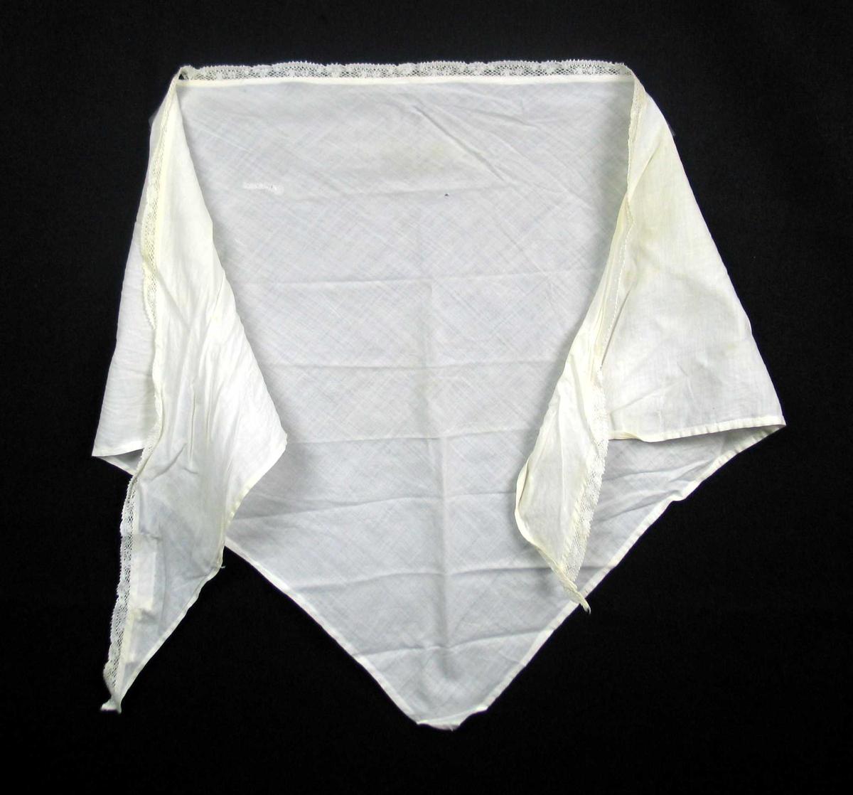 Hvitt trekantet tørkle i to-skaft vevd bomull med påsydd kniplingsblonde. Blonden er antatt maskinvevd. Tørkledet er maskinfaldet på tre sider
