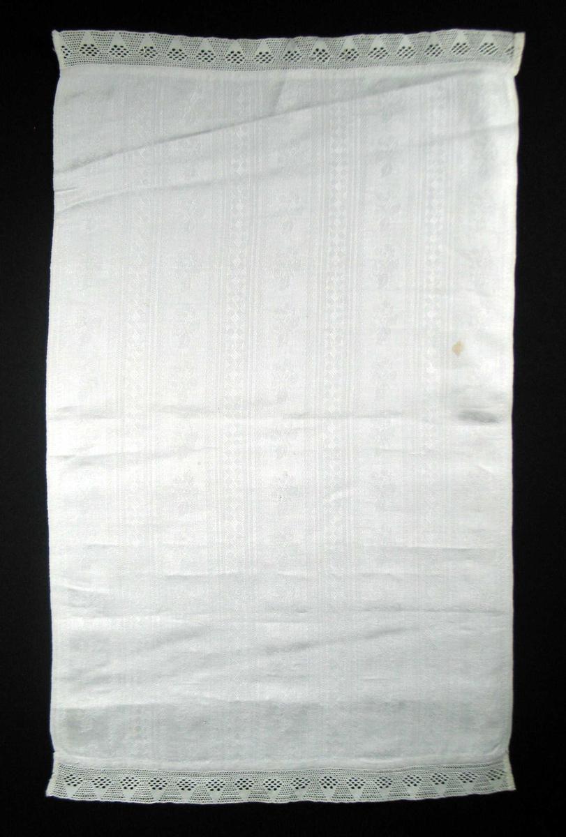 Hvit linduk med blonde påsydd i begge ender. Vevbredden er 45,5 cm. Lintøyet er stripete med border i lengderetningen. 4,5 rapport i bredden. Mellom, fast, rettvinklet oppbygd mønster med kryssfigurer, 5,5 bred er et felt med blad-og blomstmotiv hvor alle vender samme vei.