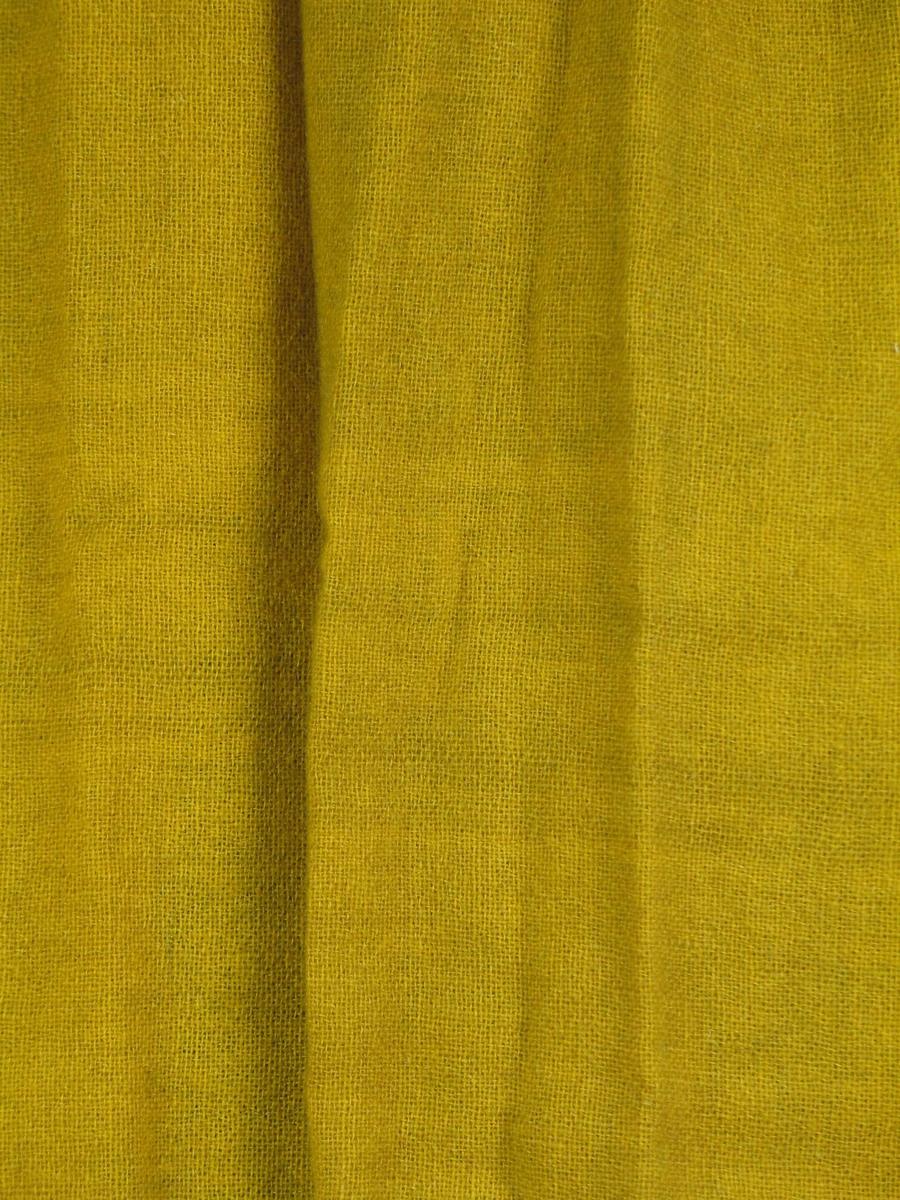 Gul gardin i to-skaft ullstoff. Vevbredden er 136 cm, jare i sidene. 4 cm fald nederst, og 2,5 cm fald øverst, isydd metallringer som ble tredd inn på en metallstang.