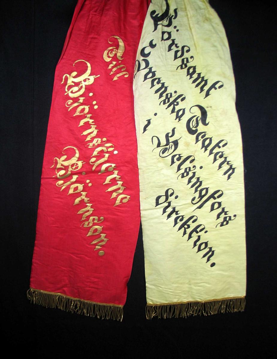 Begravelsessløyfe i rød og hvit silke med frynser og tekst i gull og svart.