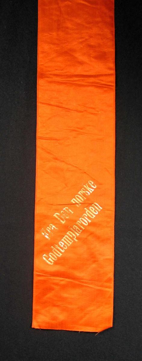 Begravelsessløyfe i oransje silke med tekst i gull.