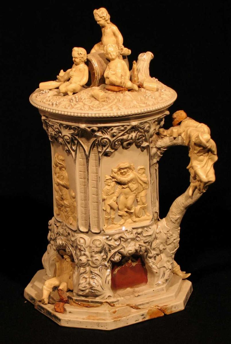 Stort, rikt dekorert krus i keramikk med beige glasur utvendig. Fotstykket er sekskantet formet som en trapp. Over fire nisjer med med drikkescener i relieff. Lokket har englefigurer omgitt av flasker, mugger og glass. Vindruer, løvverk og perlekranser. Sølvfargede dekorelementer.