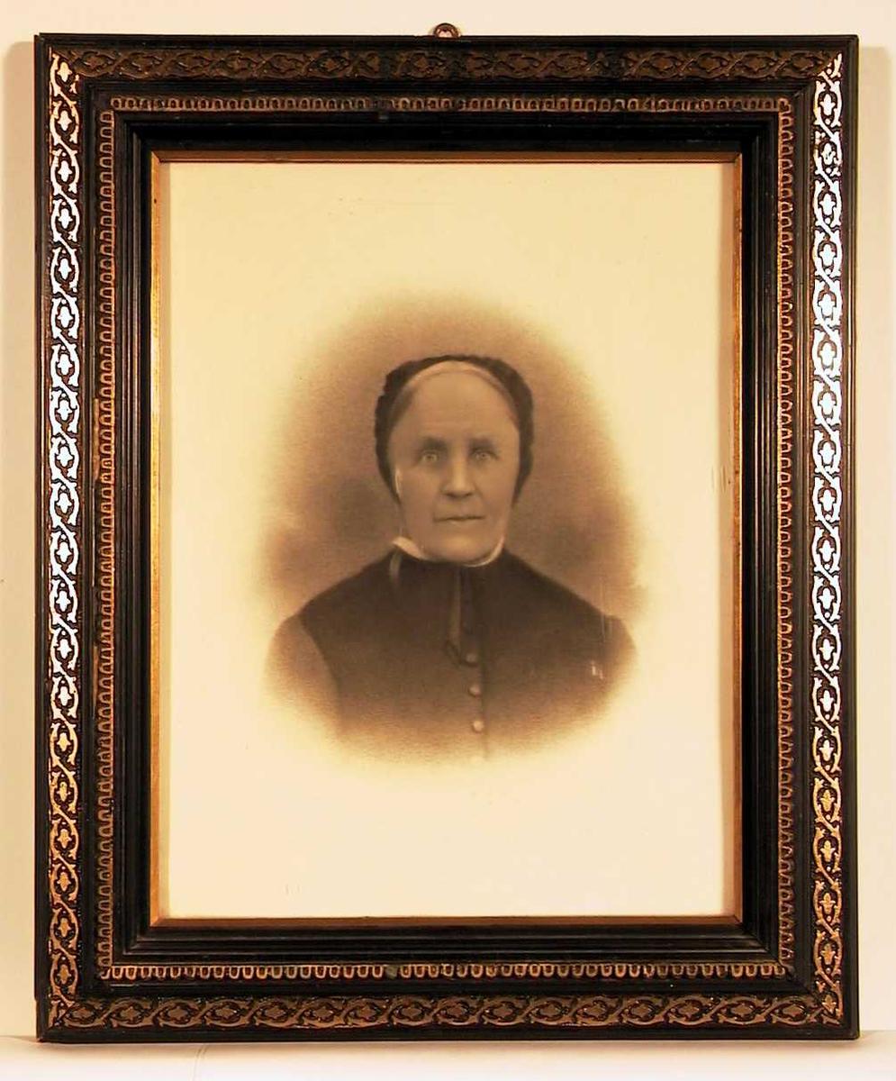 Portrett av en eldre dame. Hun bærer kyse og tilkneppet kjole.