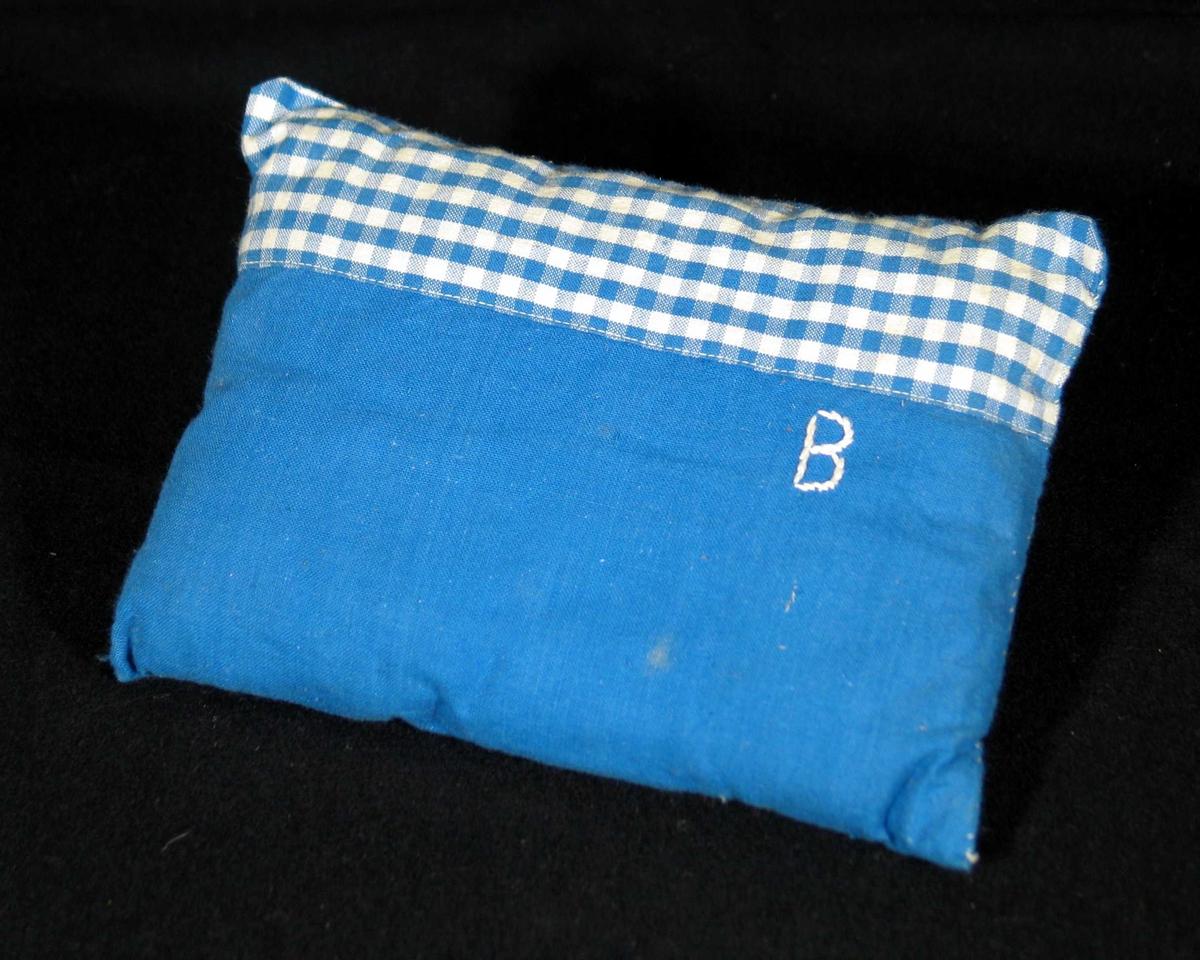 Pute til dokkeseng i blått bomullsstoff. Den har et blårutet felt øverst og en brodert B i hvitt.