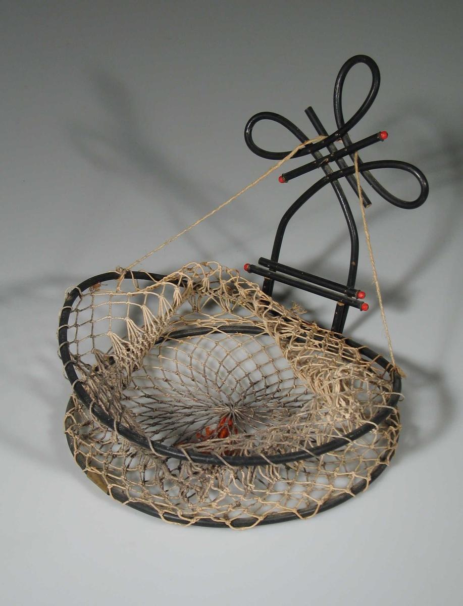 Kurv flettet av hyssing med oransje ulltråddusk under bunnen. Opphenget er av svartmalt bøyd tre med røde kuler i endene.