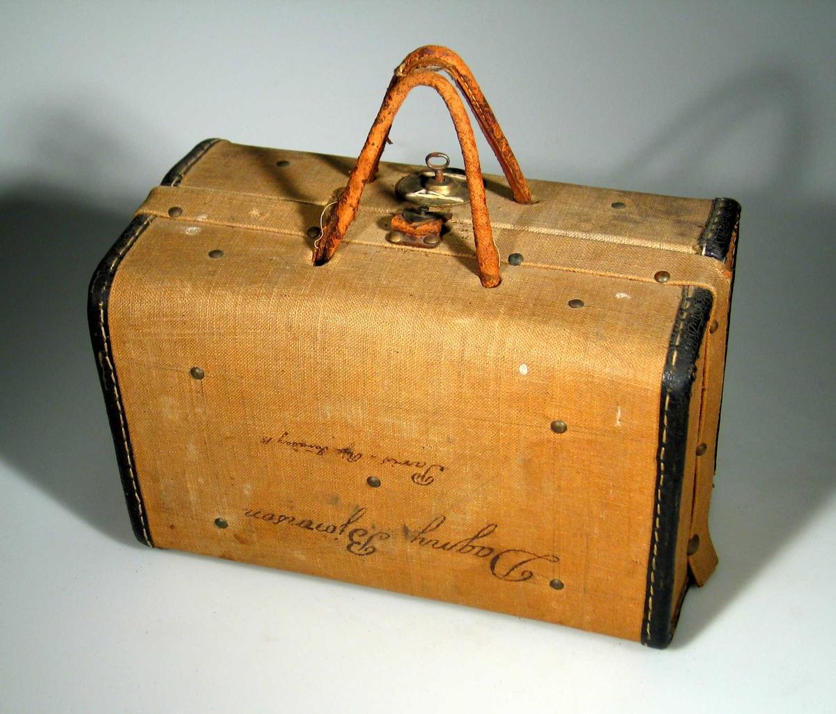Liten koffert i strietrukket kartong. Den er forsterket med skinnkanter og nagler. Kofferten har håndtak i skinn og metallås med nøkkel. Innvendig er den trukket med rødstripet papir.