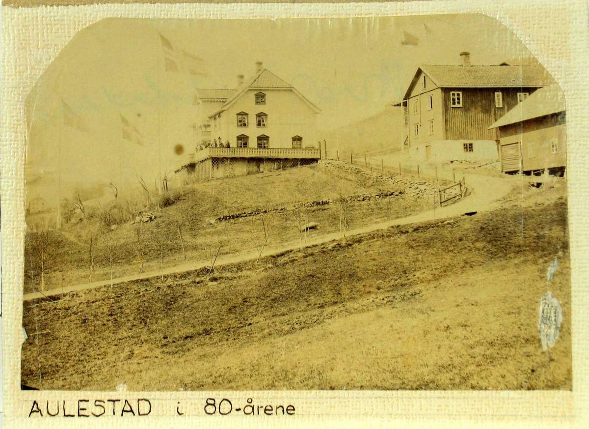 Hovedbygningen på Aulestad, mennesker på verandaen.