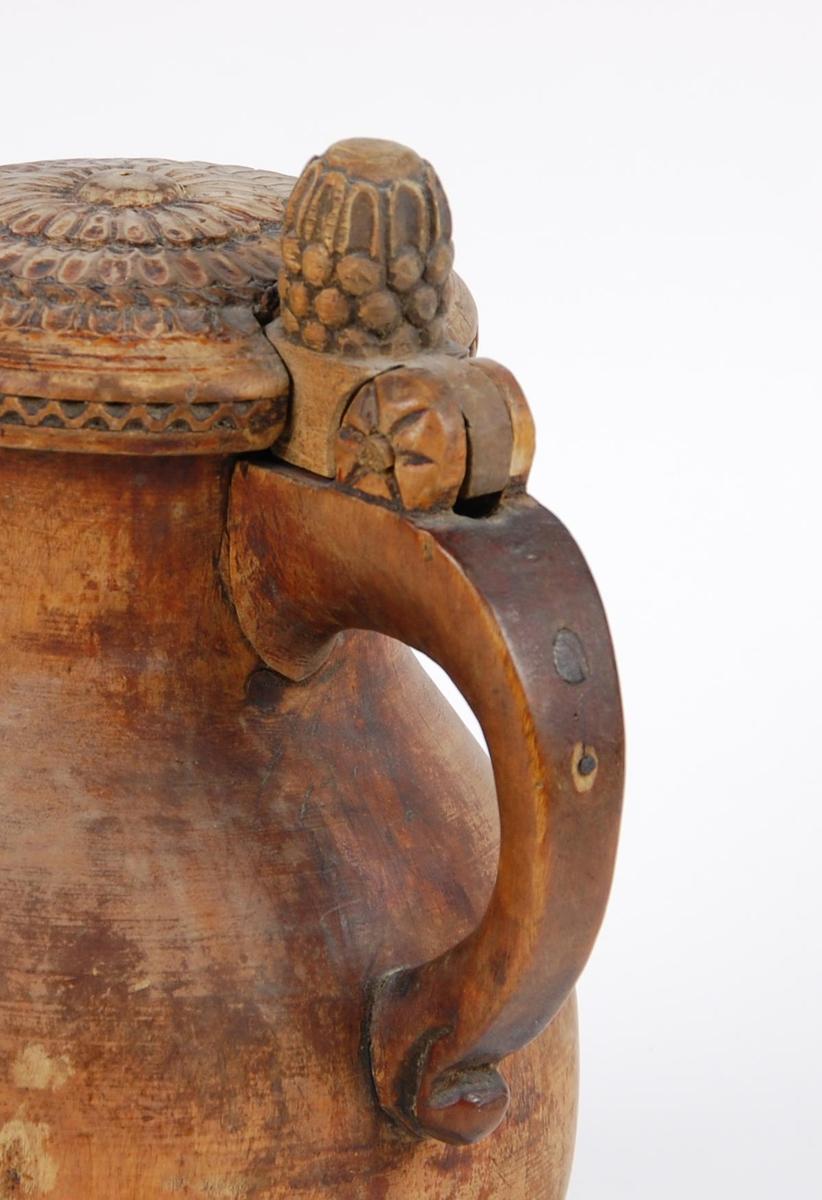 Kanne av dreid valbjørk. Lokket med to rosetter, bølgebård på yttersiden. Lokkåpner formet som en kongle. Korpus pæreformet, avskåret tut, undersiden med dreide ringer. Tre løveføtter.