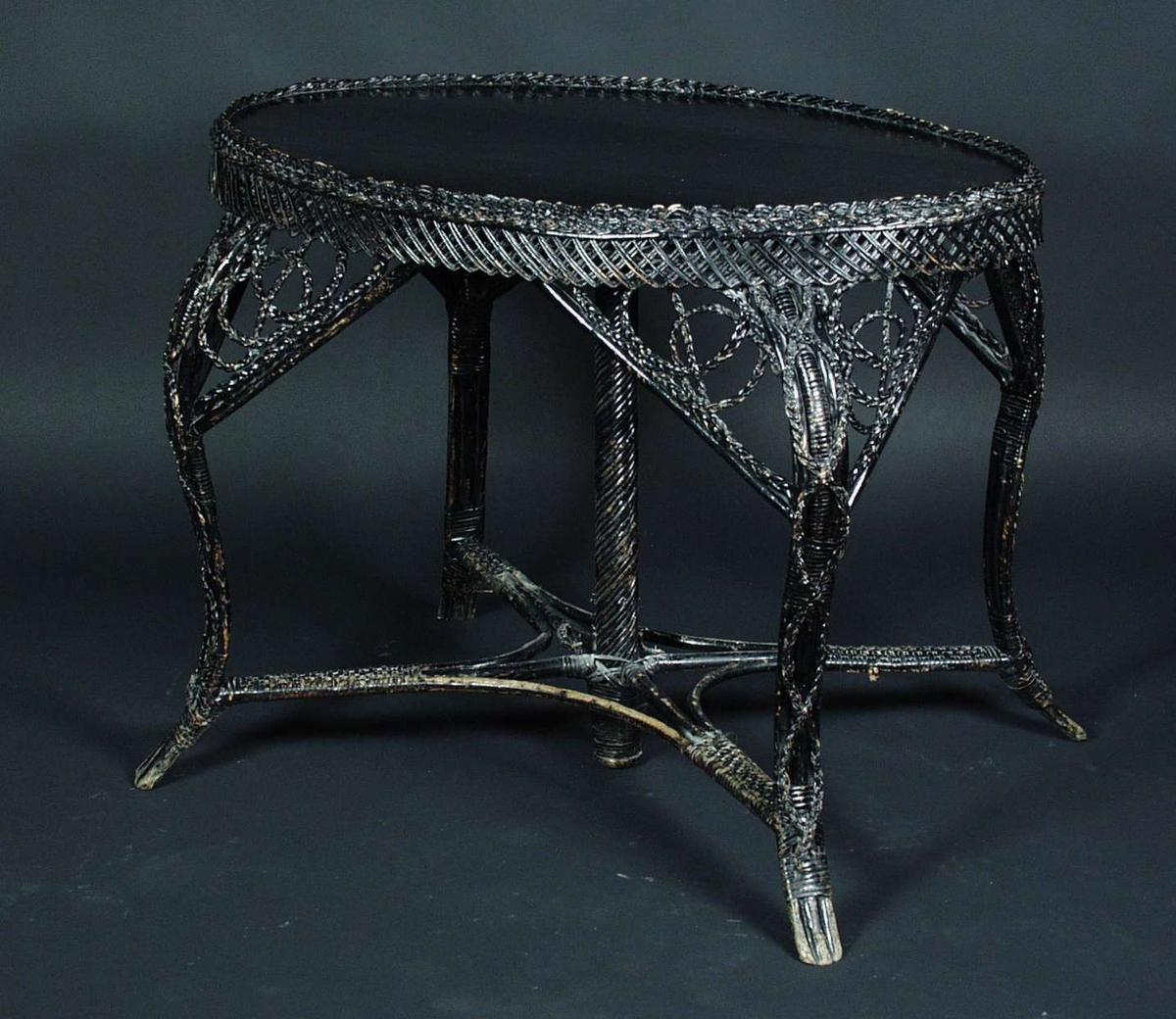 Et ovalt bord av furu og flettet pilskudd med svart maling. Bordplaten er i furu, mens sargen er flettet. Bordet har kryss under som er festet til bena En spiral søyle som er festet i bordplaten går gjennom krysset.