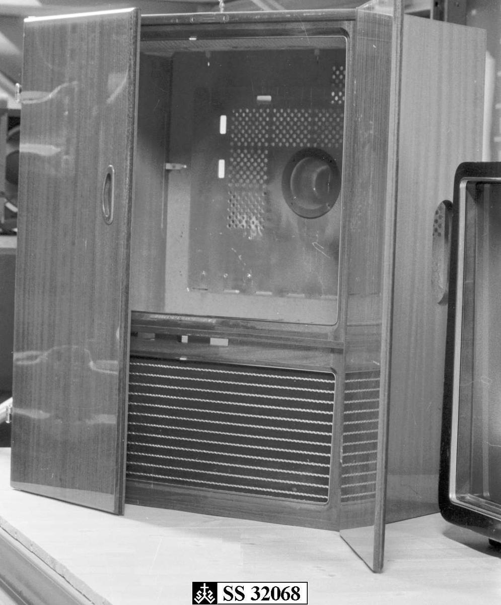 Skapet som tidligere har inneholt en TV er i polert mahogny. Når skapet er lukket skjuler de to låsbare skapdørene TVen og høytaleren under. Bakveggen er perforertmed diverse åpninger for antenne, betjeningsknapper etc. Påsatt stempelmerke bak på.
