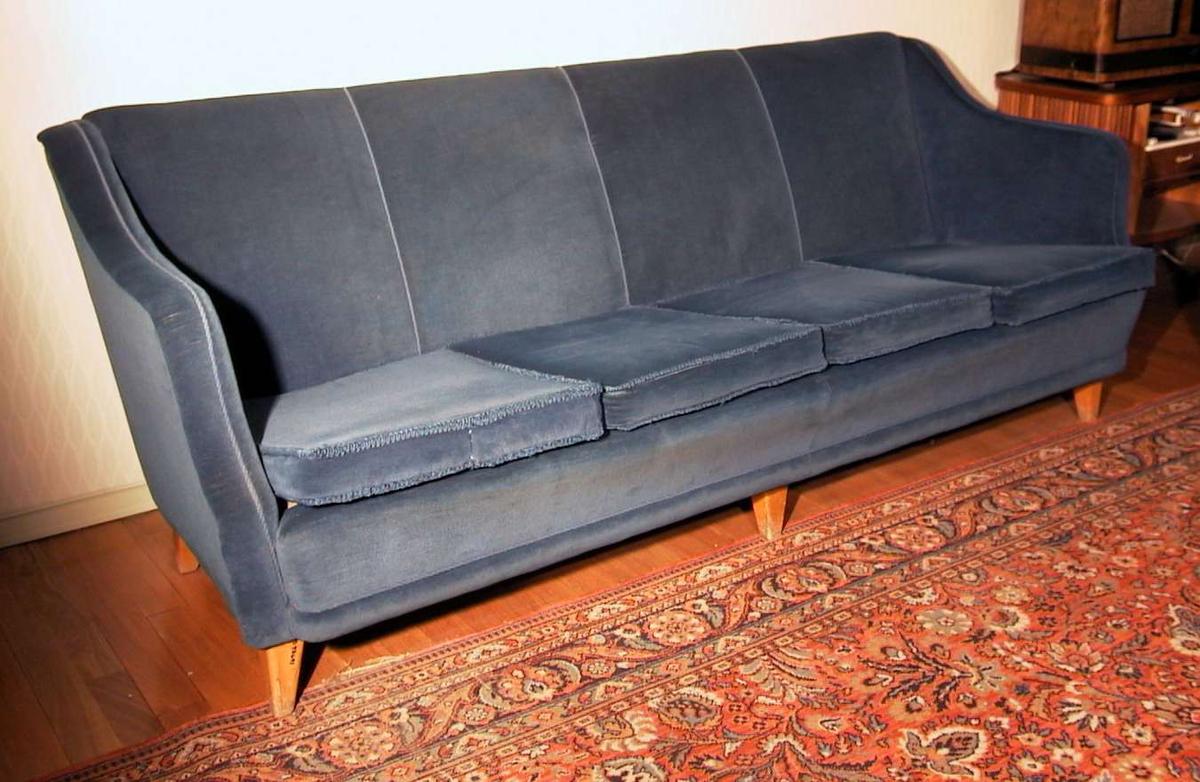 Sofa trukket i blå velur med løse puter i setet. Snorer langs kanten. Seks ben i bjørk.