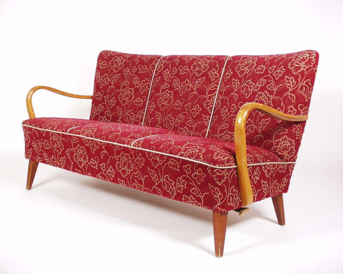 Sofaen er stoppet med rødt blomstermønstret møbelstoff, armlenene og beina er i lakkert bjørk.