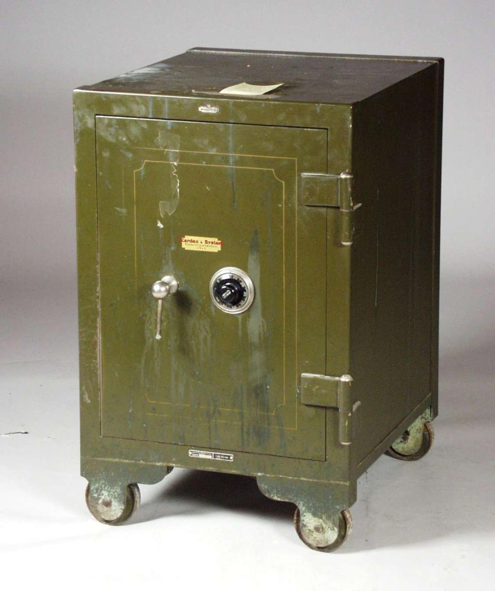 Grønt pengeskap i metall og har gyllen dekor på døra. Det står på metallhjul og har kodelås. Koden til låsen ligger ved.