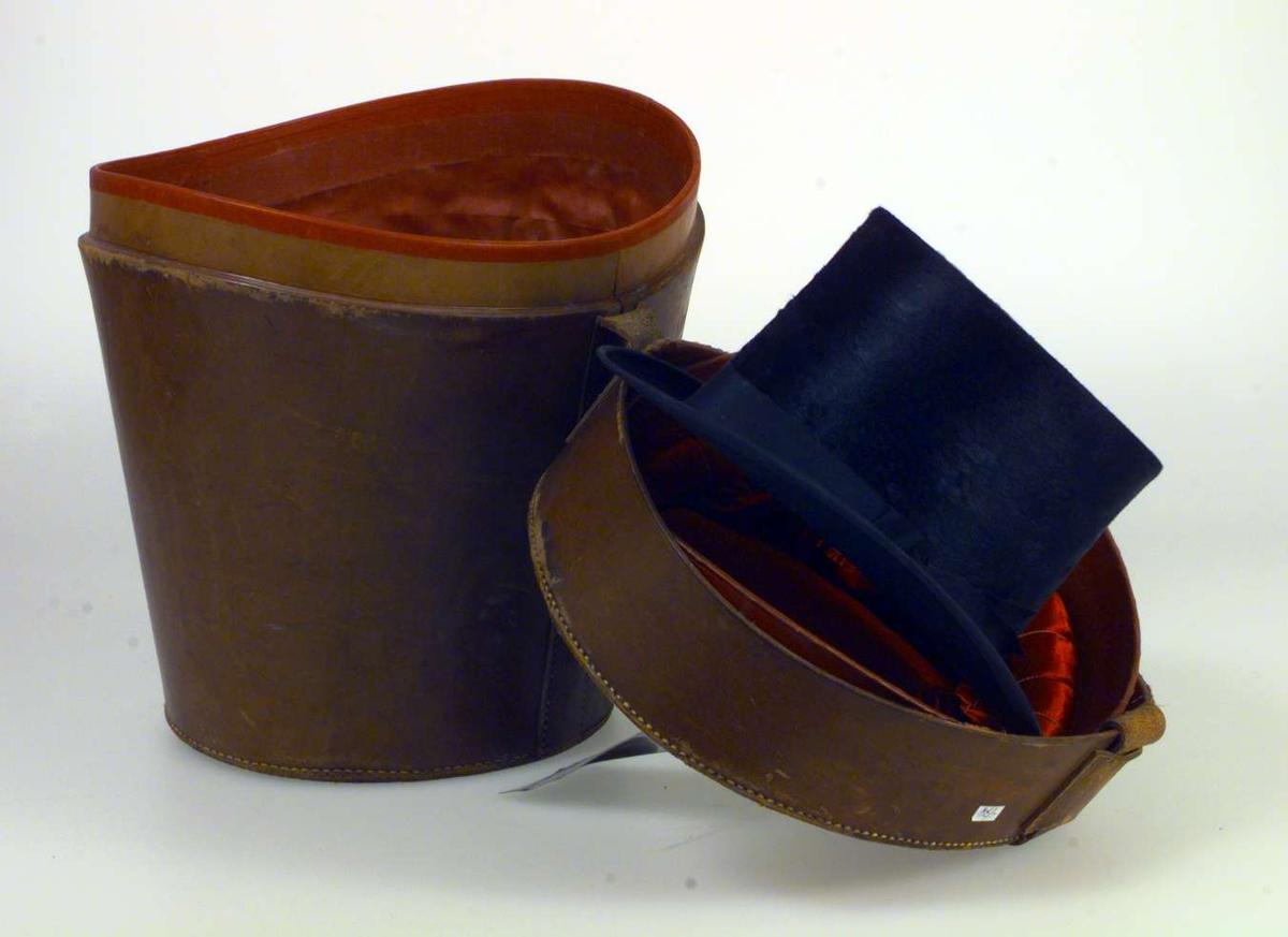 Hatteeske for flosshatt. Den er oval og har konisk form. Den er av lær og har håndtak på lokket. Den er trukket med karmosinrødt silkestoff innvendig. Lokket er festet til esken med en lærrem. Hatteesken har lås i messing. Flere mer eller mindre avrevne merkelapper er klistret på lokket. En NSB-merkelapp i metall henger i håndtaket. I hatteesken ligger en sort flosshatt som er produsert i London og importert av Kristiania Hattemagasin.
