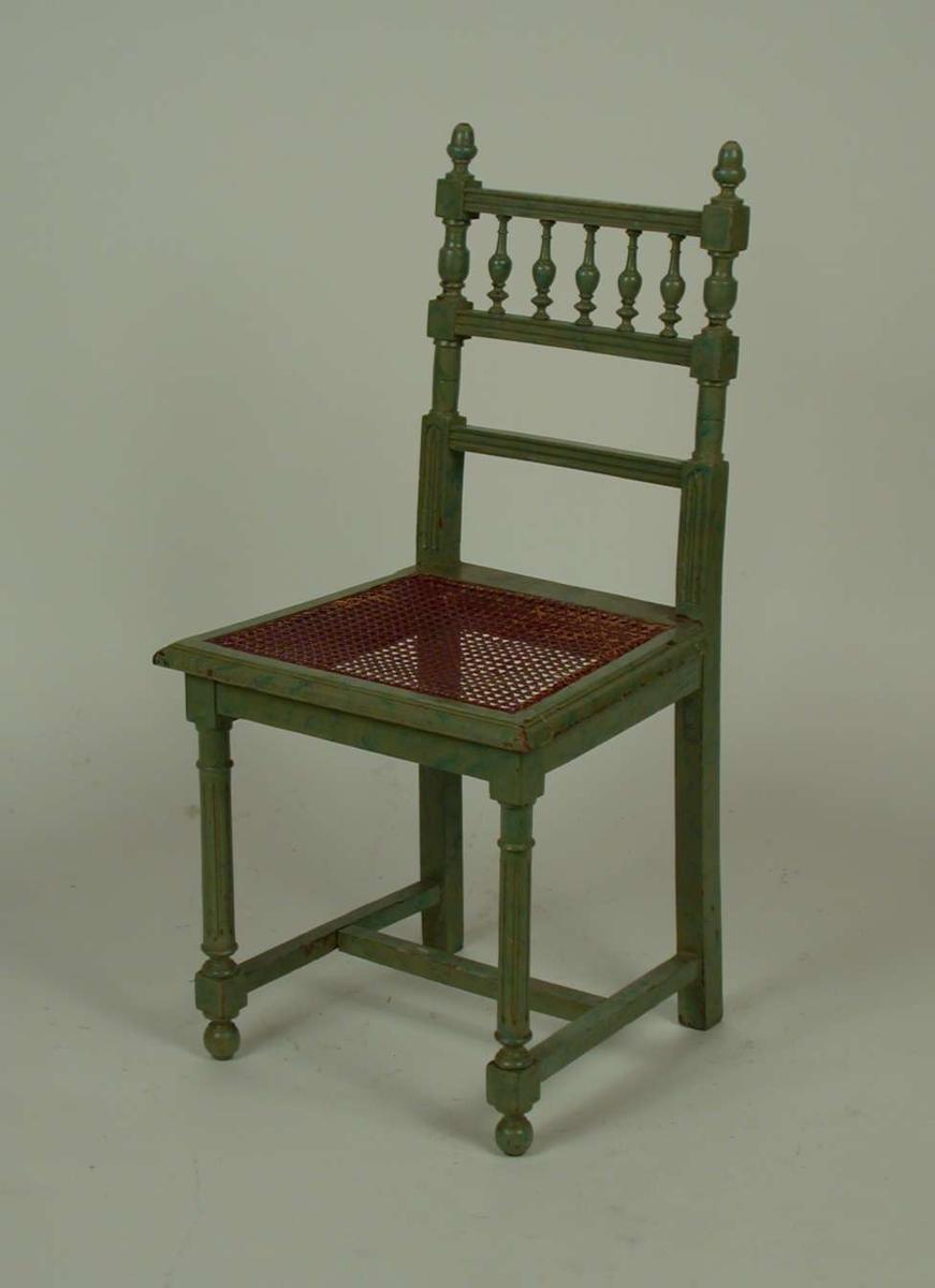 Lasert grønn stol. Setet er av rotting. Rottingen har røket.
