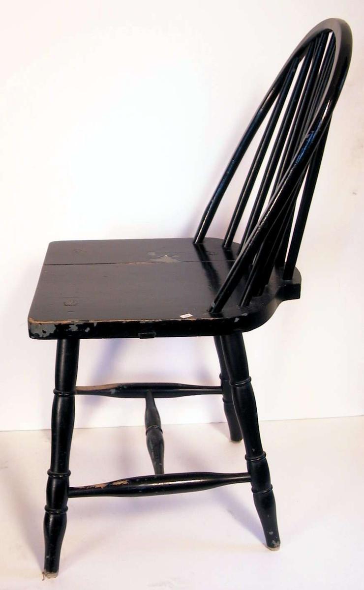 Sortmalt pinnestol med sprosser i ryggen. Setet er sprukket og malingen er avslitt.