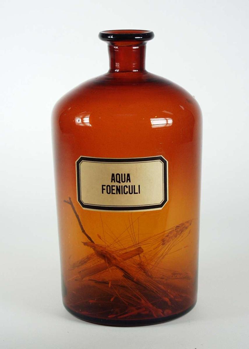 Apotekerflaske i brunt glass. Den har etikett påtrykket: Aqua Fueniculi.