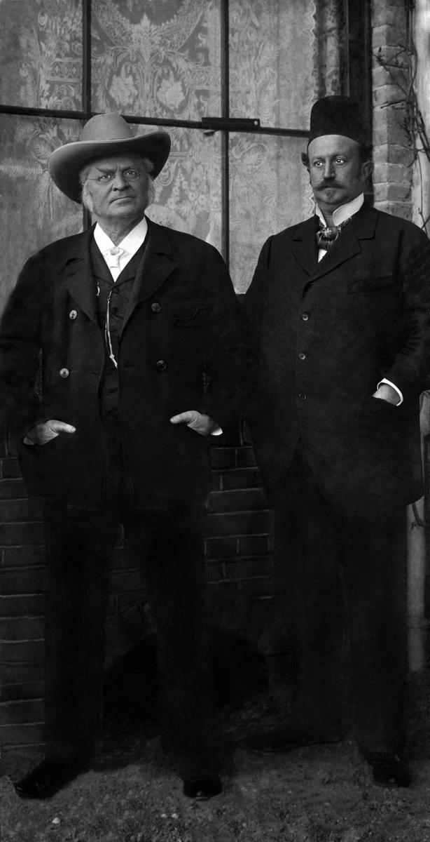 Portrett i helfigur av to middelaldrende herrer med hatt og mørk dress. Fotografiet er tatt utendørs.