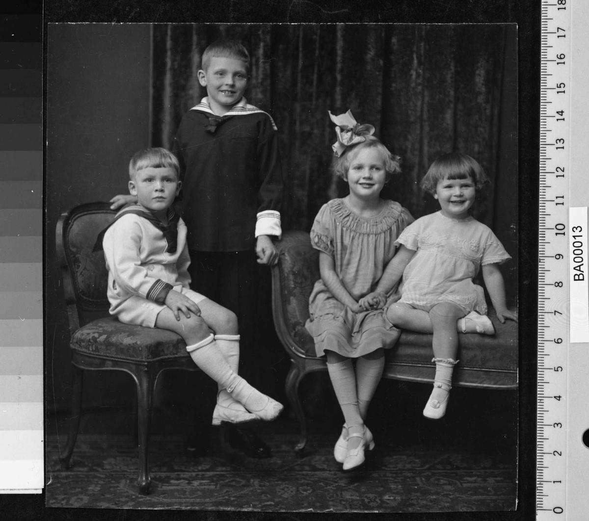 Portrettfotografi; 4 barn i forskellig alder, fra venstre: gutt i hvitt mattrostøy med korte bukser sittende på stol; stor gutt i mørkt mattrostøy med lange bukser stående litt bak; stor pike i farget staskjole, lange strømper og stor sløjfe i håret sittende på sofabenk, hun holder hånden til den lille piken ved siden av i hvitt kort kjole og halvstrømper.  Alle 4 ser på fotografen.