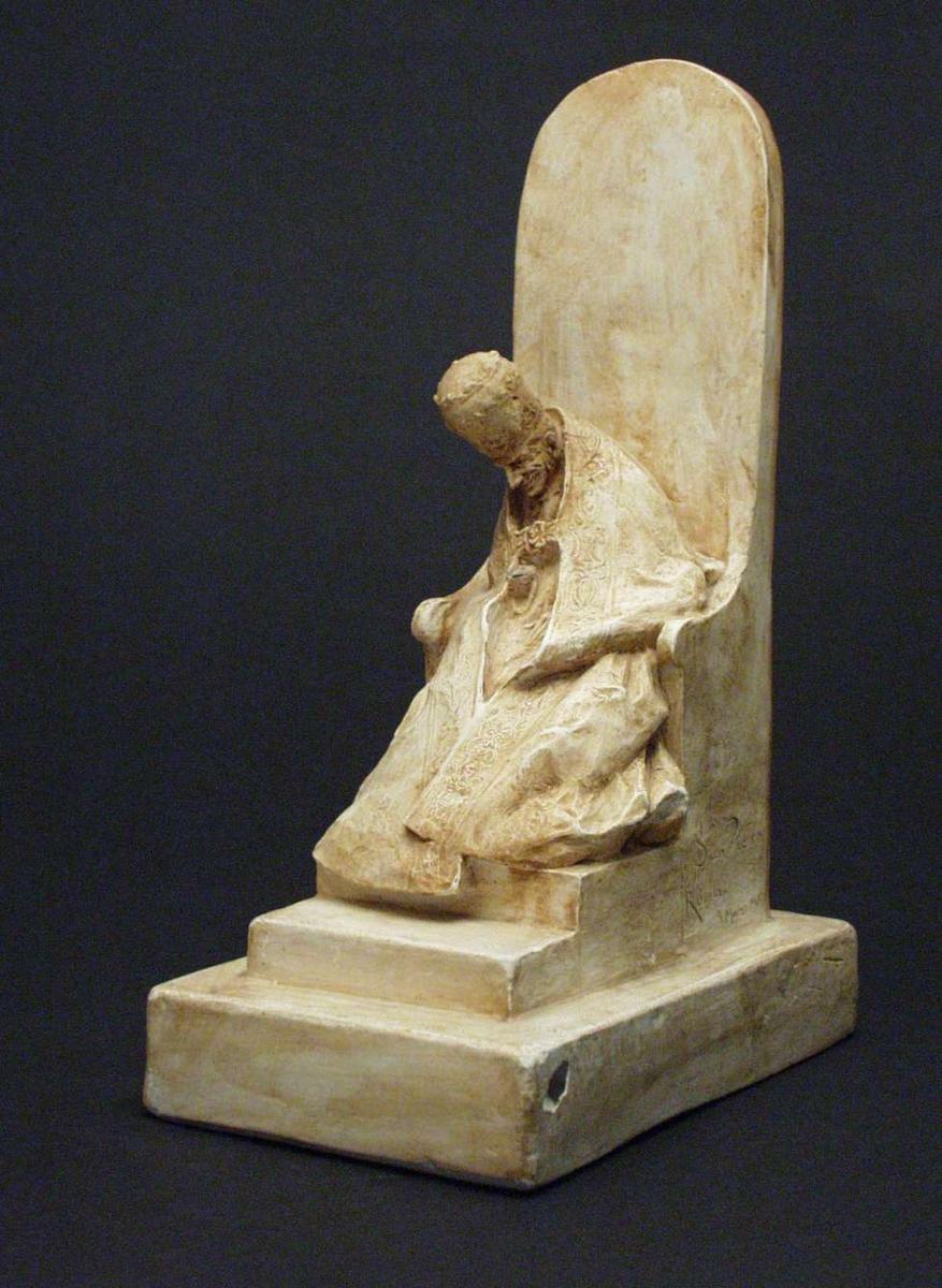 Figur støpt i gips: En mann sittende i høy pavestol på firkantet fotstykke.
