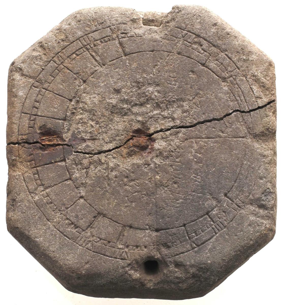 Tykk, flat 8-kantet  stein med et inndelt   sirkelbånd   innskåret  langs kanten, avslitt særlig i høyre  halvdel. Et gjennomgående hull oppe og nede.  Tilstand: Stor sprekk tvers over midten, to rustne   jern  nagler som er satt på til forsterkning. Stål  tråd festet i øvre hull.