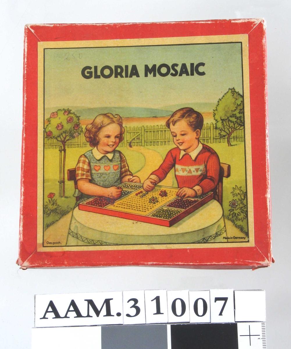 Motiv på esken: Gutt og jente ved bord i en hage, leker med liknende spill.