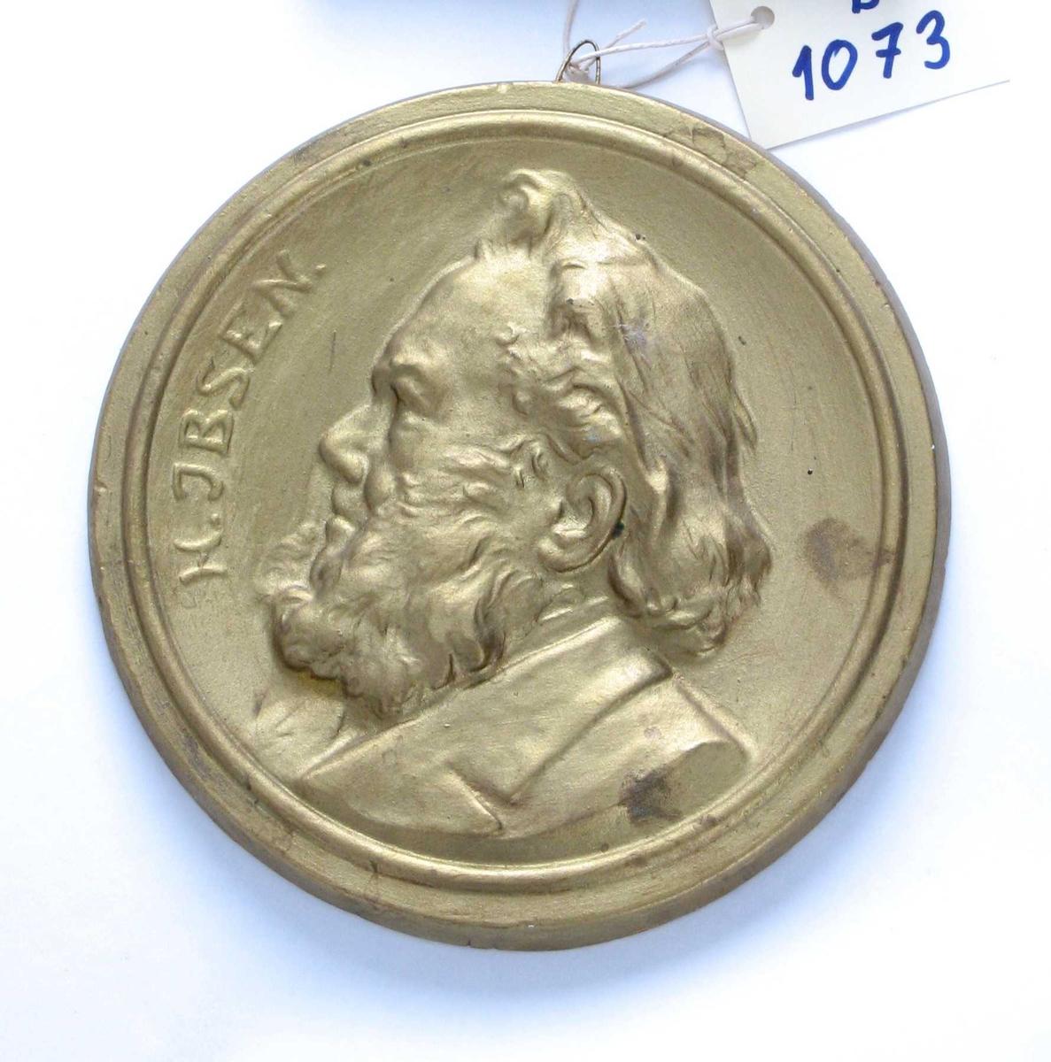 Sirkulær medaljong med   profilportrett, venstrevendt,  tekst langs venstre kant:
