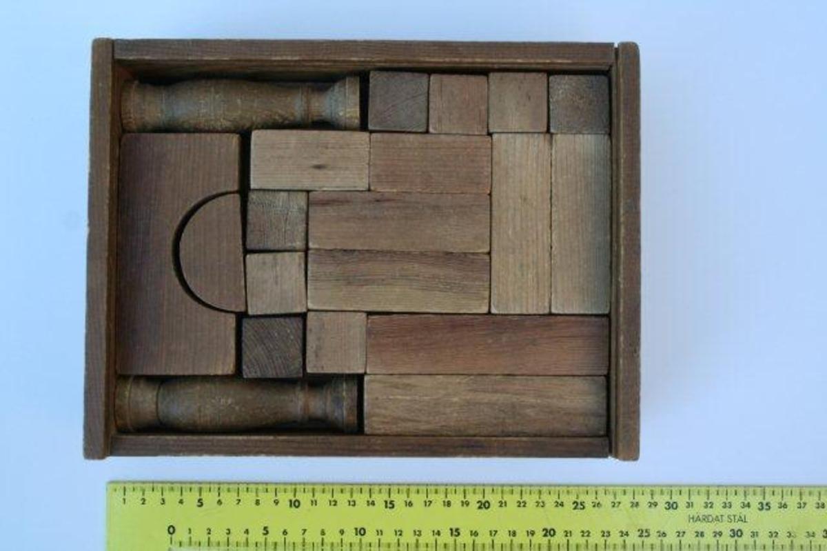 Rektangulær eske med byggeklosser av forskjellig form og størrelse. Sidekantene er stiftet sammen i hjørnene. Bunn av to tynne bord er stiftet til undersiden av rammen. Skyvelokket mangler.
