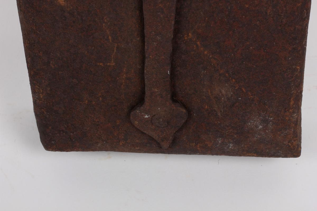 "Lokket festa til skuffa med en jernbolt og to hengsler, dreibar Til lokket og skuffa er festet jernbeslag med jernnagler, be- slaga danner nederste del av skaftet. Beslaget på lokket (som er litt kortere), kan ""låses"" fast til skuffa/beslaget med en dreibar jernnagle. Håndtak festet til tangen i skuffebeslaget, klinket, øverst en påspikret jernkrok og jernring."