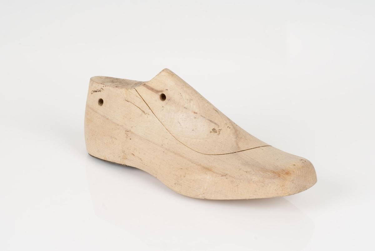 En tremodell i to deler; lest og opplest/overlest (kile). Høyrefot i skostørrelse 39, og 9 cm i vidde. Hælstykket av metall.