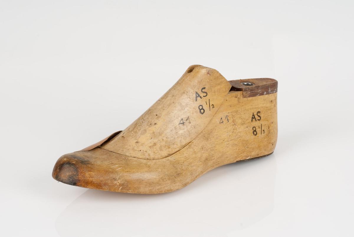 En tremodell i to deler; lest og opplest/overlest (kile). Venstrefot i skostørrelse 41, og 8,5 cm i vidde. Hælstykket av metall. Lestekam av skinn. Lærhusk på lesten.