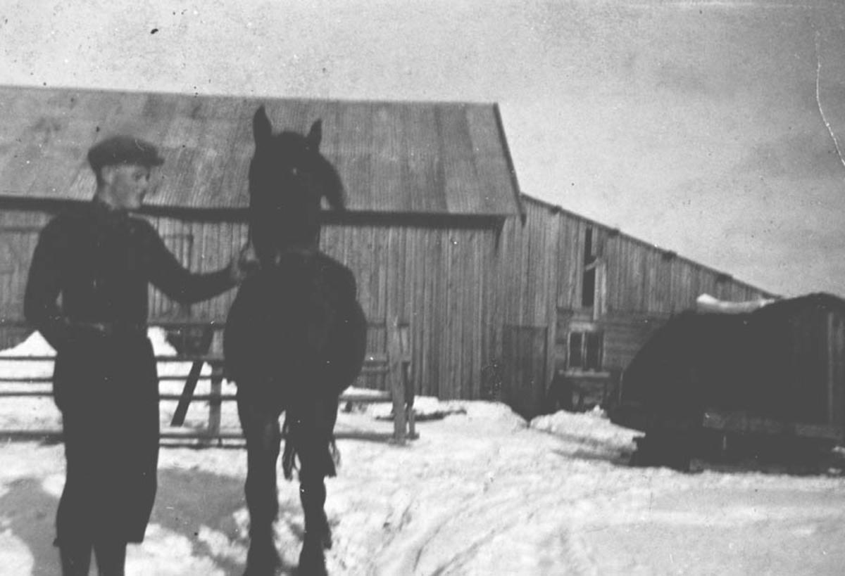 Gårdsmann med hest foran låve.