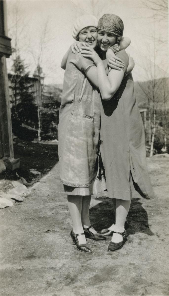 To damer i kjole gir hverandre en klem. Hage.