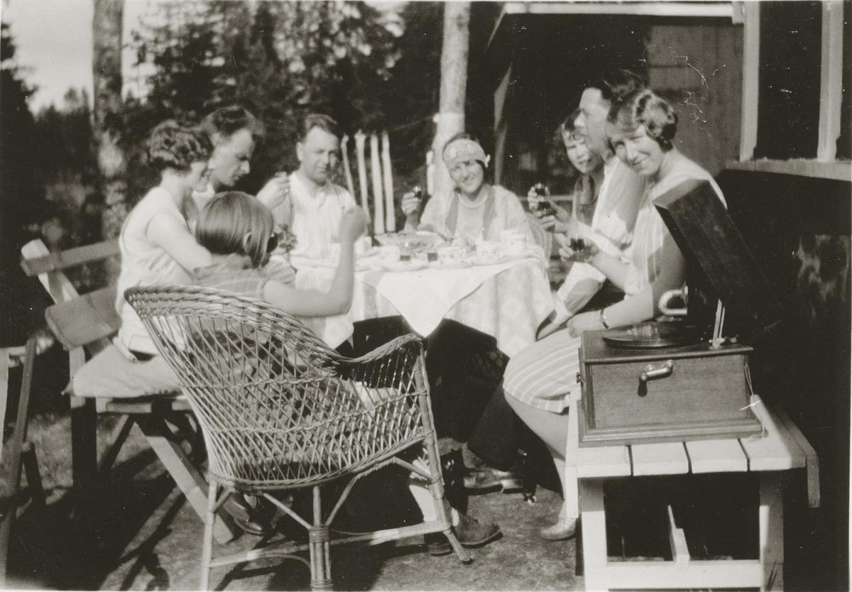 En gruppe mennesker koser seg ute på terassen. Grammofon.