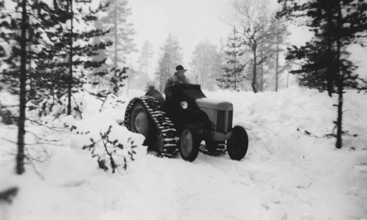 Traktor med tilleggsutstyr i snøen.