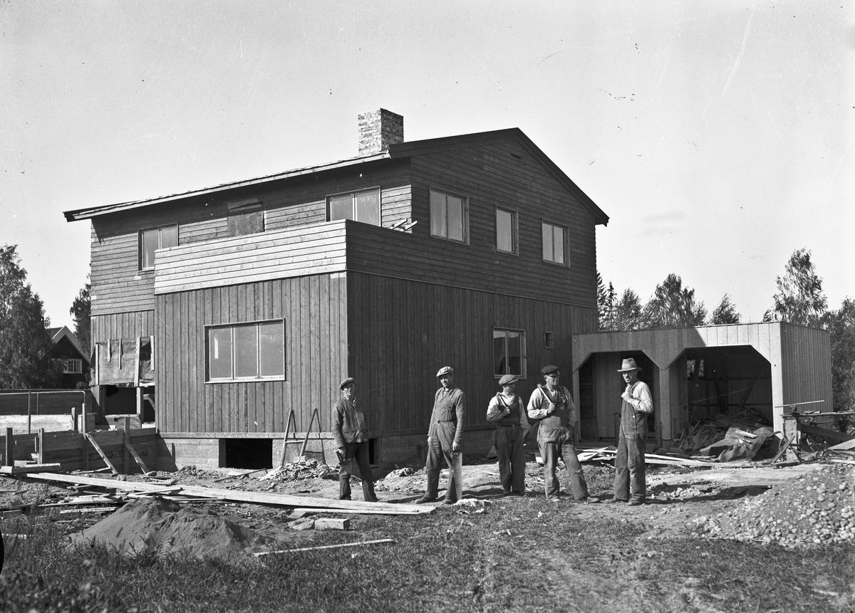 Hus under bygging. Byggmester August Bergerud helt til høyre.