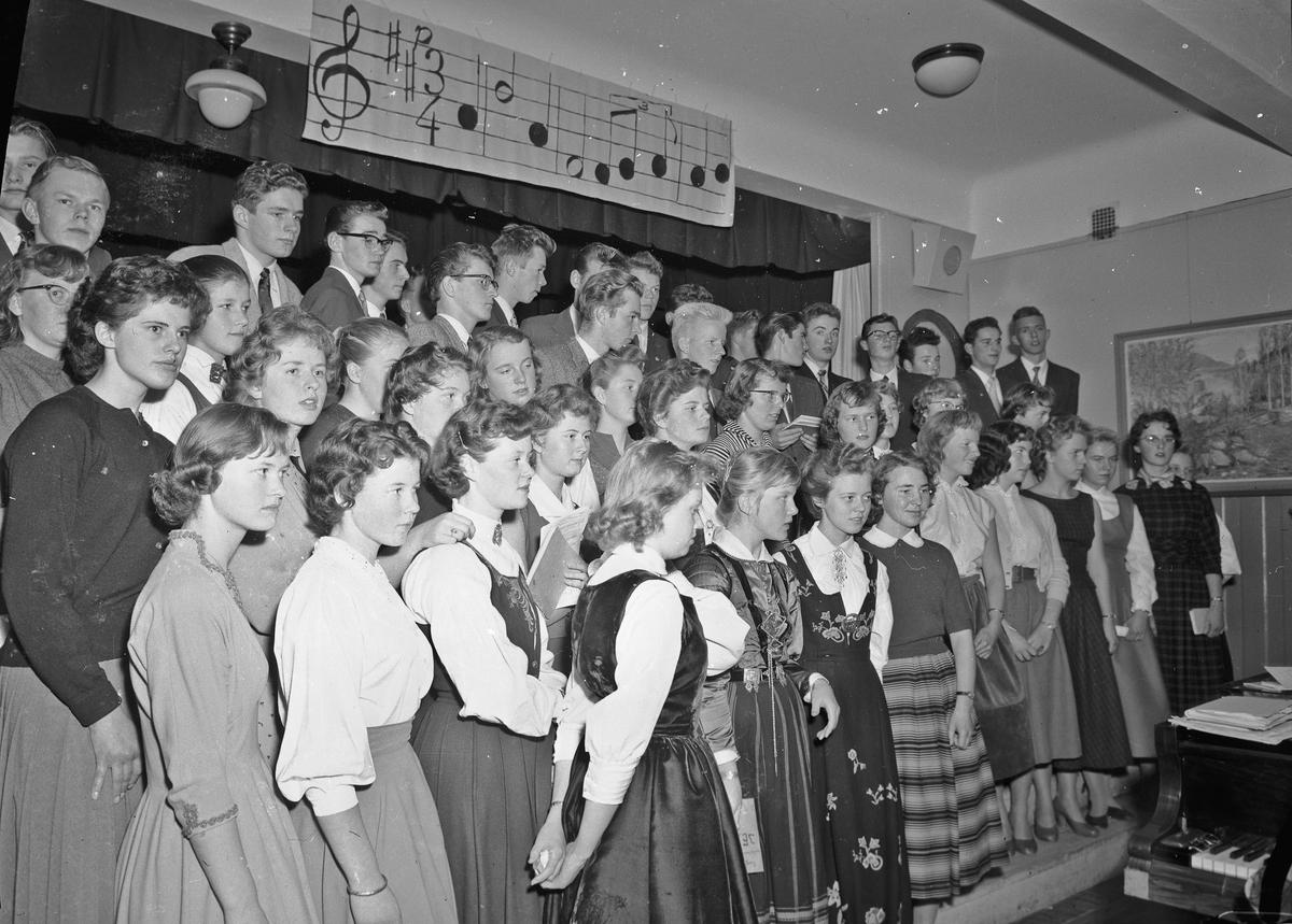 Sangtime/underholdning på gymnaset(?) Lærer Brekke helt til v.. Roald Haugen bak i Mariusgenser.