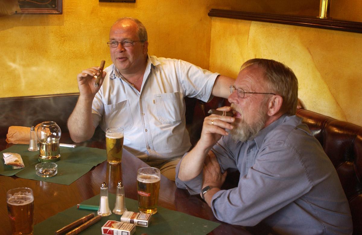 2 menn ved et bord med sigarer. Bowler & Spisepub.