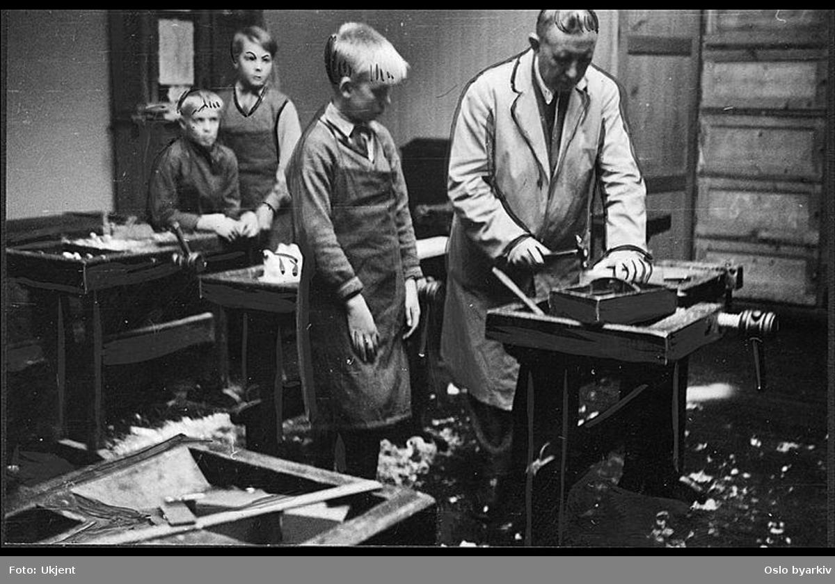 """Sløydlæreren instruerer elev. Fotografiet er forsøkt """"retusjert"""" på. Albumtittel: """"Sofienberg skole femti år - første september 1933."""""""