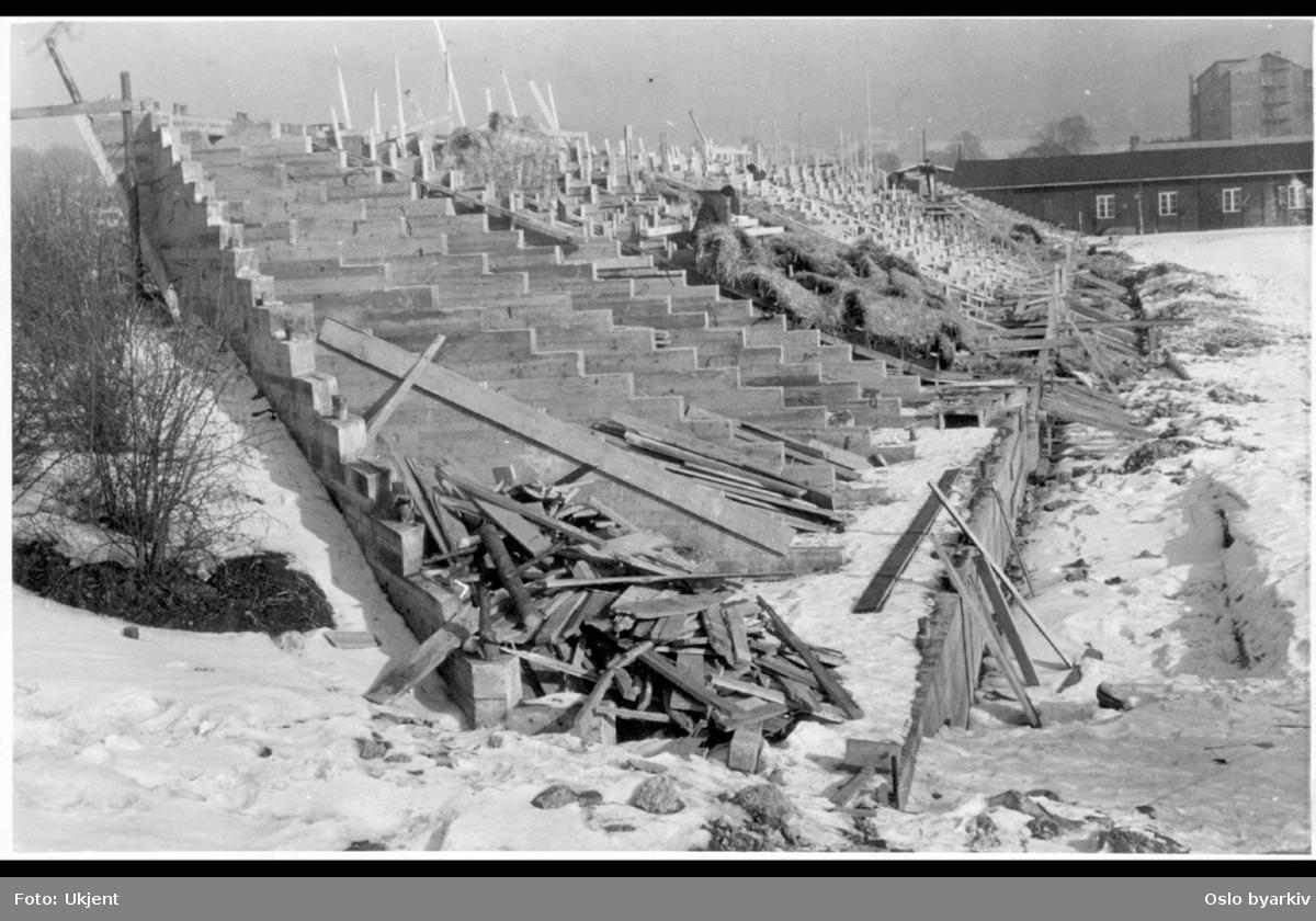 """Bygging av tribune til Voldsløkka fotballstadion. I bakgrunnen brakker (fra krigen). helt bakerst bygges hybelhuset på Lisa Kristoffersens plass. Albumtittel: """"Vålerengen Viktoria"""" (terrasse)"""