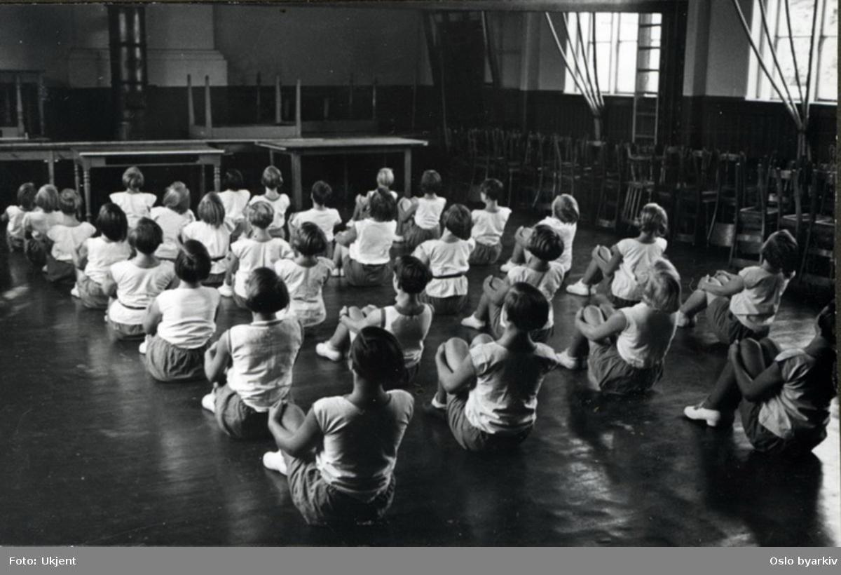"""Pikeklasse i utfoldelse i skolens gymnastikksal. (linjegymnastikk)Albumtittel: """"Sofienberg skole femti år - første september 1933."""""""